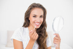 Smiling attractive brunette applying lip gloss and holding mirror Stock Photo