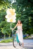 Smiling attractive brunette holding ballons while driving blue bike on park alley. Smiling attractive brunette in long white dress holding colorful balloons and Stock Images