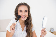 Smiling attractive brunette holding a brush and a mirror Royalty Free Stock Photo