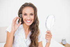 Smiling attractive brunette holding an eyelash curler and mirror Royalty Free Stock Photos