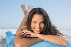 Smiling attractive brunette relaxing on her lilo. Smiling attractive brunette on the beach relaxing on her lilo Royalty Free Stock Images