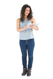 Smiling attractive brunette using her tablet Stock Images