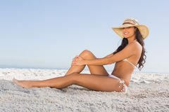 Smiling attractive brunette in white bikini posing while sitting Royalty Free Stock Images