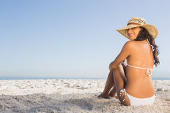 Smiling attractive brunette in white bikini sitting Royalty Free Stock Images