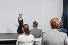 Smiling attractive business coach gesturing during training. In hub royalty free stock photography