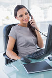 Smiling attractive businesswoman answering phone Stock Images