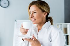 Smiling attractive businesswoman drinking coffee. In office royalty free stock photos