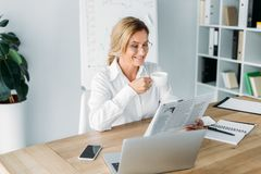 Smiling attractive businesswoman drinking coffee and reading newspaper. In office royalty free stock photos