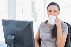 Smiling attractive businesswoman drinking tea Stock Image