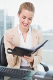 Smiling attractive businesswoman holding her agenda Royalty Free Stock Photo