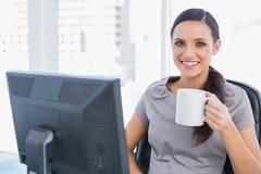 Smiling attractive businesswoman holding mug Stock Image