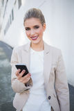 Smiling attractive businesswoman sending a text Royalty Free Stock Image
