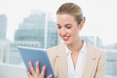 Smiling attractive businesswoman using her tablet Stock Images