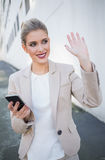 Smiling attractive businesswoman waving Stock Images