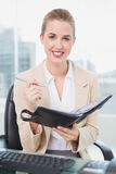 Smiling attractive businesswoman writing on her agenda Royalty Free Stock Photography