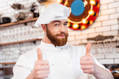Smiling attractive chef cook showing thumbs up Royalty Free Stock Photos