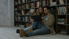 Smiling student couple using tablet pc in library. Smiling attractive couple in headphones working on digital tablet pc while sitting on floor in campus library stock video footage