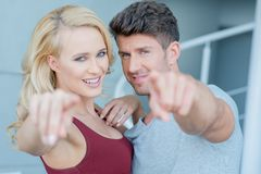 Smiling attractive couple pointing at the camera Stock Photo