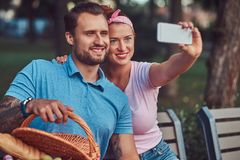 Attractive happy couple taking selfie at a picnic in a park, during dating outdoors. Smiling attractive couple taking selfie at a picnic in a park, during Royalty Free Stock Photo