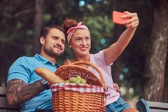 Attractive happy couple taking selfie at a picnic in a park, during dating outdoors. Smiling attractive couple taking selfie at a picnic in a park, during Royalty Free Stock Image