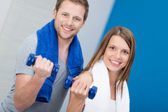 Smiling attractive couple working out in a gym. Flexing their arms while holding dumbbells to strengthen their muscles Royalty Free Stock Photo