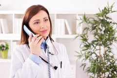 Smiling attractive female doctor talking with patient and schedu. Smiling female doctor talking with patient and scheduling Stock Photo