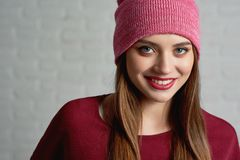 Smiling attractive female in red hat and sweater wearing beautiful professional make up posing to camera. Headshot of smiling attractive female in red hat and Royalty Free Stock Photo