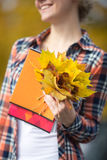 Smiling attractive female young student outdoors holding yellow leaves Royalty Free Stock Photography