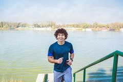 Smiling attractive fitness man runner running upstairs royalty free stock image