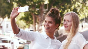 Smiling attractive friends taking selfie. Outdoor stock video footage