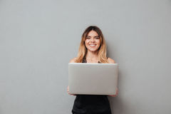 Smiling attractive girl holding laptop computer and looking at camera Stock Photography