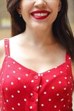 Smiling attractive girl in red polka dots dress in park. Close up stock image