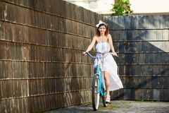 Smiling attractive girl riding blue bike down paved old city street. Smiling attractive girl in white dreess riding vintage blue bike on paved street with dark Stock Image