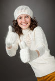 Smiling attractive girl showing thumbs up in mittens Royalty Free Stock Photo