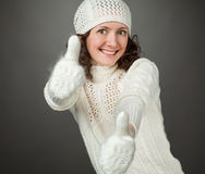 Smiling attractive girl showing thumbs up in mittens Royalty Free Stock Images
