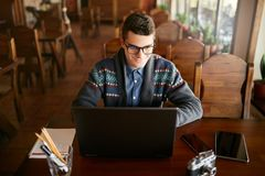 Smiling attractive hipster man in glasses and winter sweater working on laptop in cafe. Freelancer businessman browsing Royalty Free Stock Photography