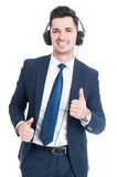 Smiling attractive lawyer doing thumbup gesture and listening mu Stock Photography