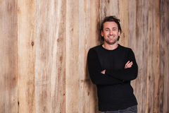 Smiling attractive man in black jumper standing with hands folded. Smiling attractive young man in black jumper standing with hands folded over wooden background Stock Photos