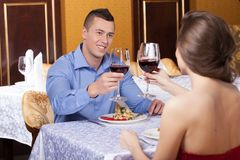 Smiling attractive man drinking wine with woman. Stock Images