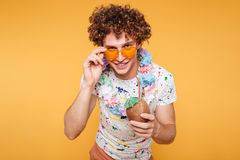 Smiling attractive man in summer clothes holding coconut cocktail. And looking over his sunglasses at camera isolated over yellow background Royalty Free Stock Image