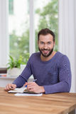Smiling attractive man working at home stock photos