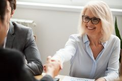 Smiling attractive mature businesswoman handshaking businessman. At meeting negotiation, happy hr senior executive women shaking hand welcoming new hire partner royalty free stock image