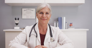 Smiling attractive mature female doctor talking to camera patient POV Stock Images