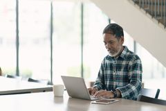 Smiling attractive mature man with white, grey stylish short beard using smartphone gadget serving internet in modern office,co-wo. Rking space or coffee shop royalty free stock photography