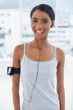 Smiling attractive model in sportswear listening to music Royalty Free Stock Images