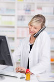 Smiling attractive pharmacist talking at the phone Stock Image