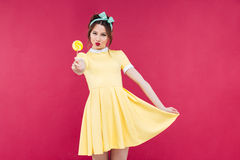 Smiling attractive pinup girl in yellow dress showing sweet lollipop Stock Photos