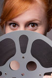 Smiling attractive redhead looking over film reel. Happy attractive redhead peeking over the top of a film reel Stock Images