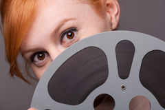 Smiling attractive redhead looking over film reel Royalty Free Stock Images