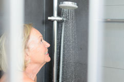 Smiling attractive senior woman taking a shower Stock Images